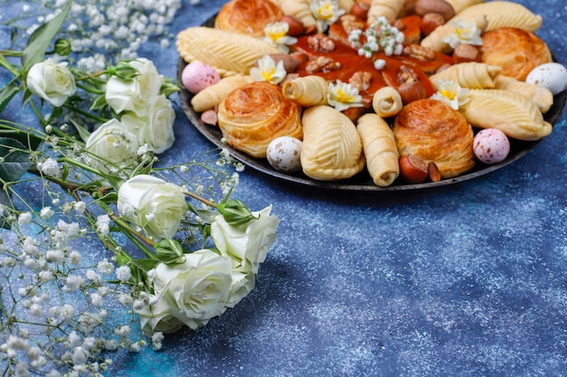 Traditionelle aserbaidschanische feiertags-novruz-kekse baklavas und shakarburas auf schwarzer tablettplatte