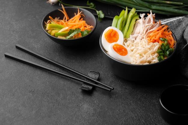 Traditionelle asiatische nudeln mit eiern, gemüse und stäbchen