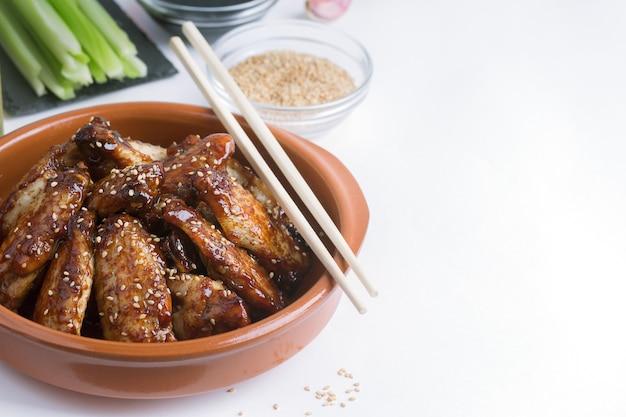 Traditionelle asiatische pfannengerichte hühnerflügel mit sesam und gemüse