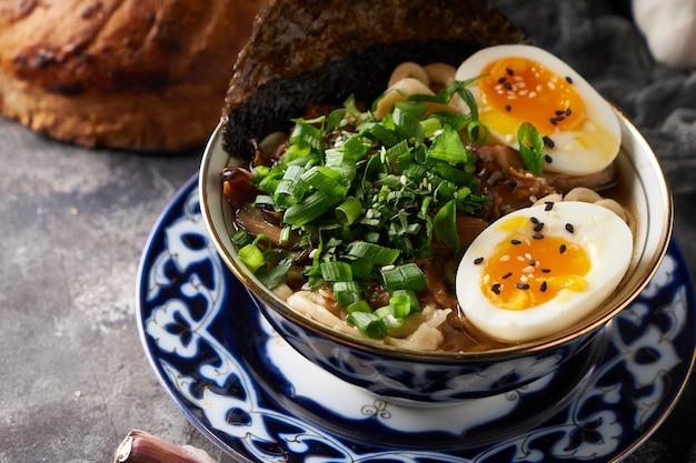 Traditionelle asiatische ramen-nudelsuppe mit huhn und eiern auf grauem hintergrund