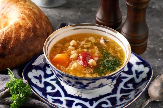 Traditionelle asiatische shurpa-suppe in der traditionellen verzierungsschale auf strahlhintergrund