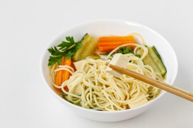 Traditionelle asiatische suppe mit tofukäse, nudeln, karotten und zucchini. dieses gericht enthält normalerweise bouillon und gemüse