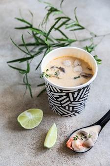 Traditionelle asiatische suppe tom yum kung in einem einwegbecher aus kraftpapier suppe zum mitnehmen von speisen