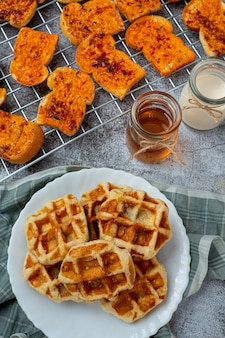 Traditionelle belgische waffeln, blutorangen und blaubeeren dressing und tasse kaffee für süßes frühstück, zusammensetzung auf hellem hintergrund.