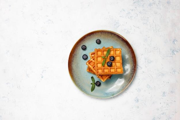 Traditionelle belgische waffeln mit frischen beeren und honig auf grauer betonoberfläche.