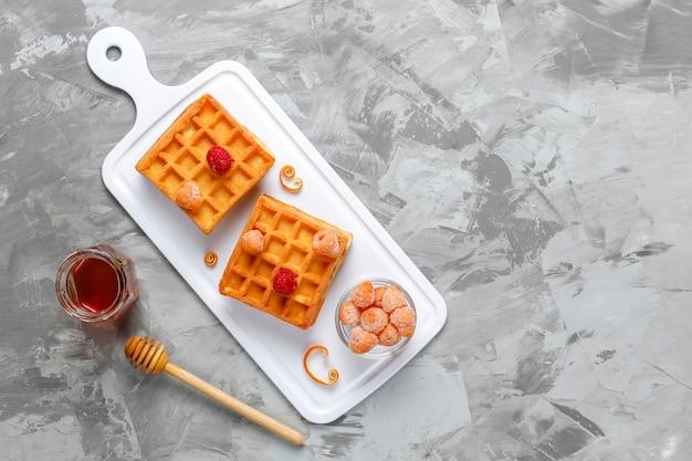 Traditionelle belgische waffeln mit honig und gefrorenen beeren.