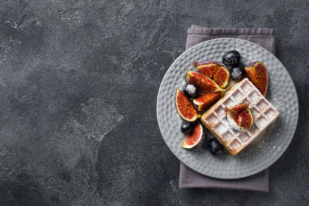 Traditionelle belgische waffeln mit puderzuckertrauben und feigen.
