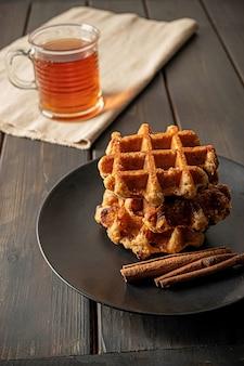 Traditionelle belgische waffeln, serviert mit zimtstangen und einer tasse tee zum frühstück. zusammensetzung auf dunkler holzoberfläche.