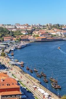 Traditionelle boote mit weinfässern auf dem fluss douro in der portugiesischen stadt porto.