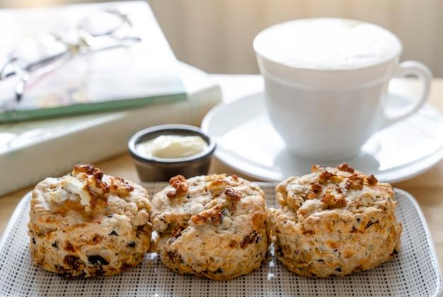 Traditionelle britische käse scones mit verschwommener tasse kaffee und buch, frisch gebackene scones englische brötchen mit hellem licht morgens oder nachmittags im frühling oder sommer