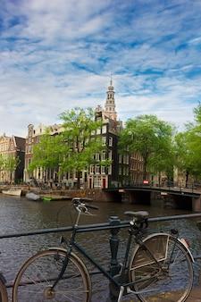 Traditionelle brücke mit fahrrad und alten häusern am kanal in amsterdam, niederlande