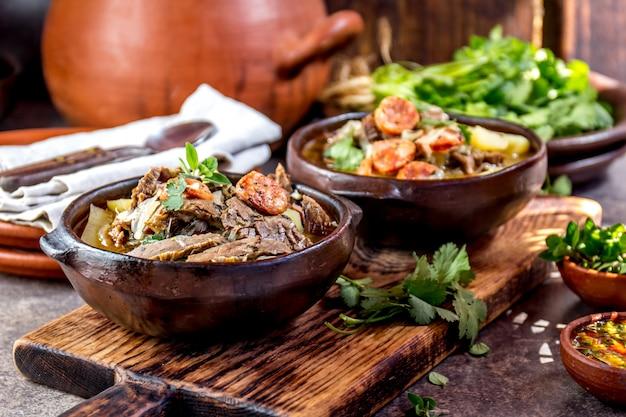 Traditionelle chilenische suppe mit gegrilltem fleisch, zwiebeln und kartoffeln in tonplatten serviert