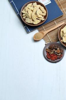Traditionelle chinesische medizin und alte medizinische buch auf weißem schreibtisch