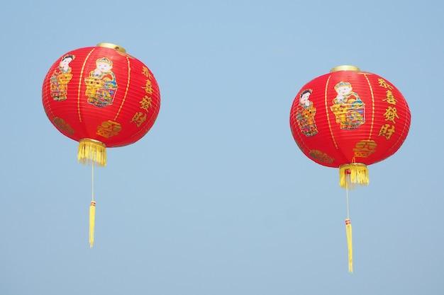 Traditionelle chinesische neujahrslaterne mit namen geschrieben in der chinesischen kalligraphie im blauen himmel