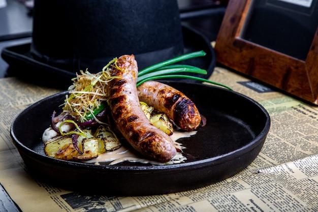 Traditionelle deutsche würste mit der kartoffel gedient in der wanne. restaurant gericht. seitenansicht