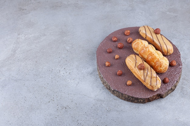 Traditionelle einfache eclairs mit haselnüssen auf einem holzstück.