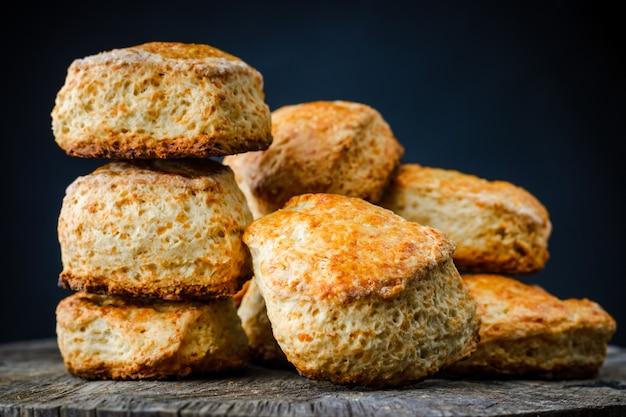Traditionelle englische käsebrötchen scones auf holztisch auf dunklem hintergrund