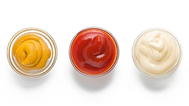 Traditionelle fast food- und barbecue-saucen. ketchup, senf, mayonnaise in glasschalen auf weiß