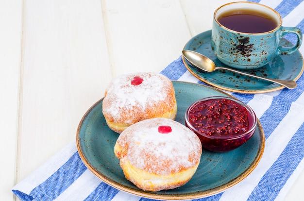 Traditionelle food donuts mit puderzucker und marmelade. konzept jüdischer feiertag chanukka.