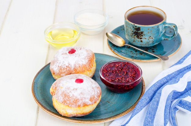 Traditionelle food donuts mit puderzucker und marmelade. konzept und hintergrund jüdischer feiertag chanukka.