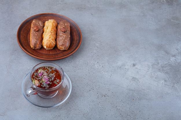 Traditionelle französische eclairs mit schokolade und einer glas tasse tee.