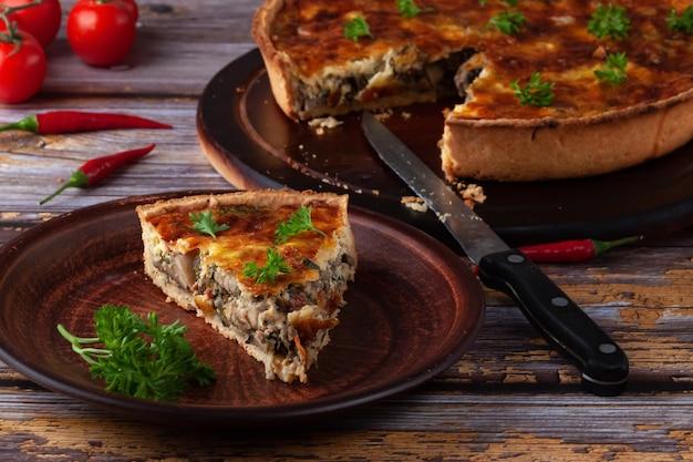 Traditionelle französische quiche-torte mit huhn und pilz auf einem holztisch