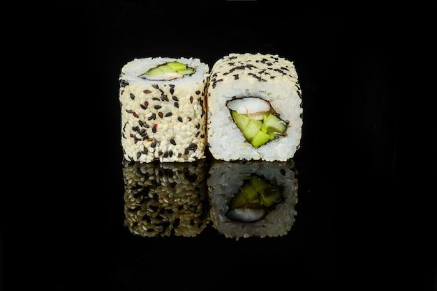 Traditionelle frische japanische sushirollen auf einem schwarzen hintergrund