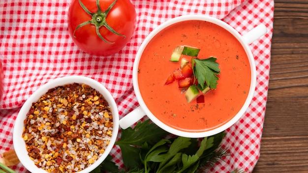 Traditionelle gazpacho auf einem holztisch mit verschiedenen gewürzen und kräutern. draufsicht.