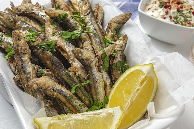 Traditionelle gebratene sardellen mit zitrone und petersilie. meeresfrüchte-konzept