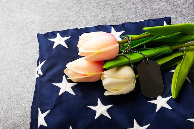 Traditionelle gefaltete flagge der vereinigten staaten von amerika, etikett und tulpenblume, gedenkerinnerung und dankeschön des helden