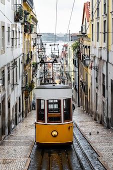 Traditionelle gelbe straßenbahn in einer engen straße in lissabon an einem regnerischen wintertag, mit dem fluss tajo im hintergrund defokussiert.