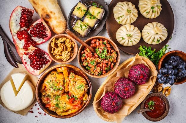 Traditionelle georgische küchentabelle. khinkali, phali, chahokhbili, lobio, käse, aubergine rollt auf weißer tabelle.