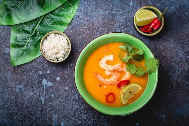 Traditionelle gesunde thailändische suppe tom yum mit garnelen, limette, koriander in schüssel auf rustikalem hintergrund mit weißem reis, overhead-schuss. authentisches thai-food-konzept food