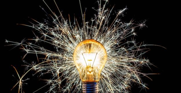 Traditionelle glühbirne mit filament und funken. schwarze wand. stromkonzept.