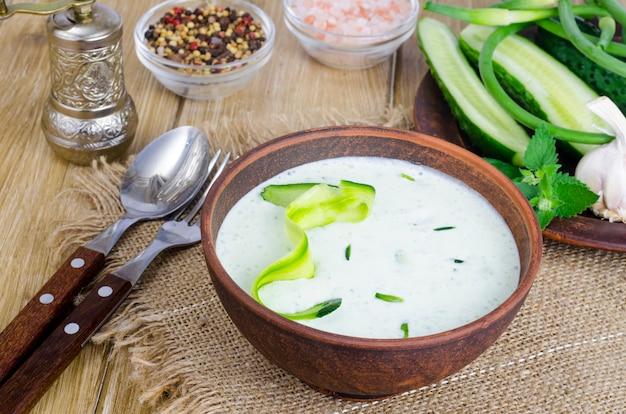Traditionelle griechische dip-sauce oder dressing tzatziki zubereitet mit geriebener gurke, joghurt, olivenöl und frischem dill auf holztisch in keramikschale.