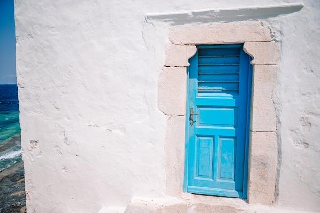 Traditionelle häuser mit blauen türen in den schmalen straßen von mykonos, griechenland.