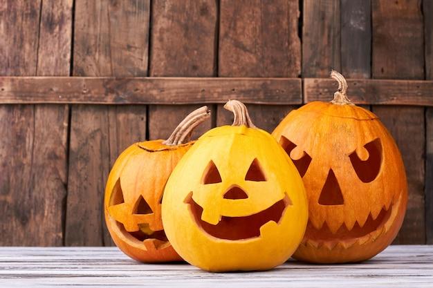 Traditionelle halloween-kürbisse auf hölzernem hintergrund.