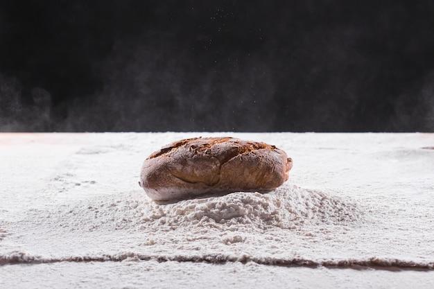 Traditionelle handwerkliche roggenbrotlaib fallen in mehl. bäckerei und hausgemachte rustikale