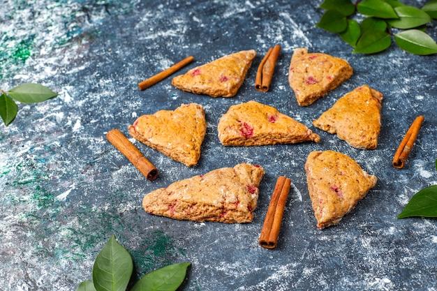 Traditionelle hausgemachte englische scones mit gefrorenen himbeeren und zimt, draufsicht