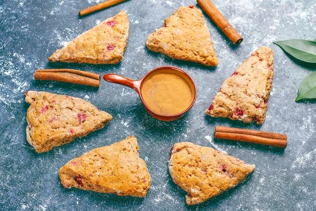 Traditionelle hausgemachte englische scones mit gefrorenen himbeeren und zimt,