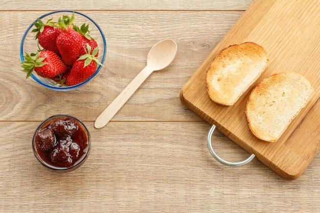 Traditionelle hausgemachte erdbeermarmelade und frische beeren in glasschalen, holzlöffel und toast auf schneidebrett auf holzschreibtisch. ansicht von oben.