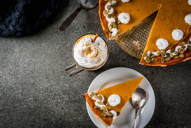 Traditionelle herbstgerichte. halloween, erntedankfest. würziger kürbiskuchen mit schlagsahne u. kürbiskernen, kürbis latte mit zimt auf schwarzer steintabelle mit decke. kopieren sie die draufsicht des raumes