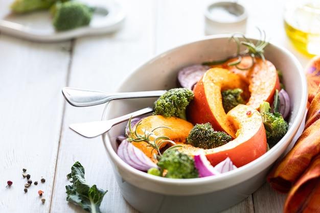 Traditionelle herbstkürbisgerichte. gegrillter gebratener kürbis mit gewürzen, olivenöl, kräutern, brokkoli und zwiebeln. auf einem backblech auf einem rustikalen hölzernen weißen hintergrund. kopieren sie platz