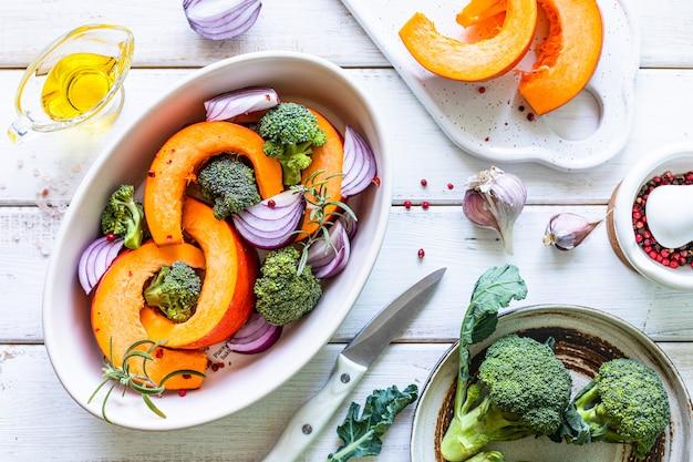 Traditionelle herbstkürbisgerichte. gegrillter gerösteter kürbis mit gewürzen, olivenöl, kräutern, brokkoli und zwiebeln. auf einem backblech draufsicht.
