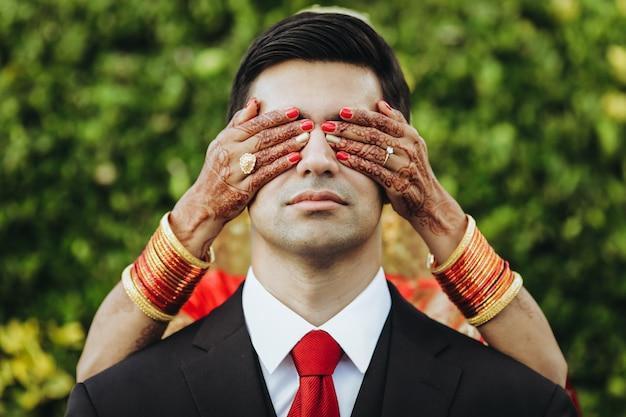 Traditionelle hinduistische hochzeit. braut umarmt bräutigam zart von hinten