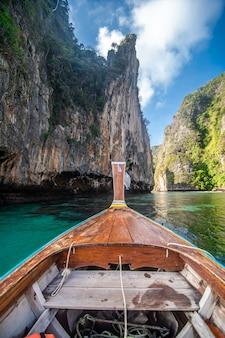 Traditionelle hölzerne longtail-taxibootnase mit dekorationsblumen und -bändern am maya bay strand gegen steile kalksteinhügel. haupthintergrund der thailändischen touristenattraktion, ko phi phi leh island