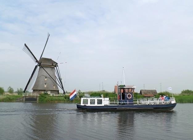 Traditionelle holländische windmühle und besichtigungsboot am kanal von kinderdijk, molenwaard, niederlande