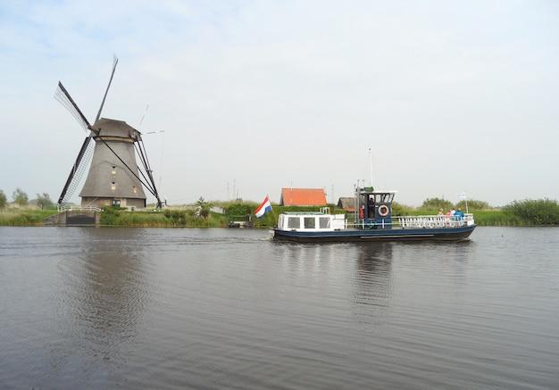 Traditionelle holländische windmühle und boot am kanal bei kinderdijk, molenwaard, niederlande