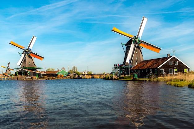 Traditionelle holländische windmühlen gelegen durch den fluss zaan, in zaanse schans, die niederlande.