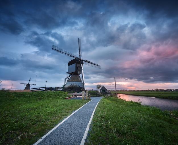 Traditionelle holländische windmühlen nähern sich wasserkanälen mit bewölktem himmel, landschaft